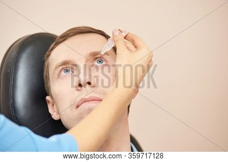 Doctor Hold Eye Drops Near Patient Face. Applying Recovery Treatment. Liquid Medicine Eyedrop Using.