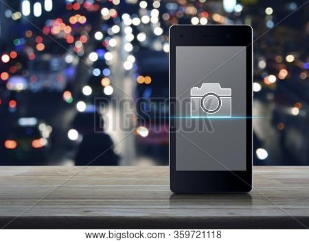 Camera Flat Icon On Modern Smart Mobile Phone Screen On Wooden Table Over Blur Colorful Night Light