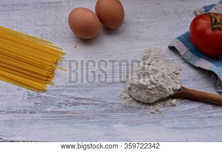 Yellow Long Spaghetti On A Rustic Background. Yellow Italian Pasta. Long Spaghetti. Raw Spaghetti Bo