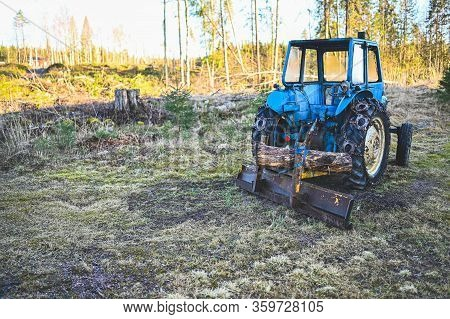 Old Blue Tractor With Plow Waiting For Snow