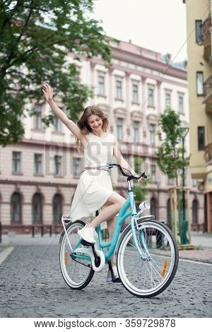 Cheerful Young Woman With Long Hair In A Light Dress Rides A Blue Retro Bicycle Along The Street Blo