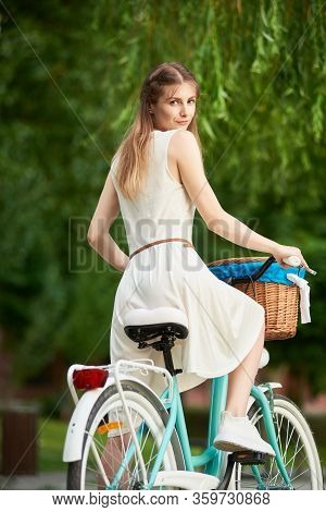 Pretty Woman On The Retro Bike With Basket At Blurred Background Greenery Of City Park. Girl Is Dres