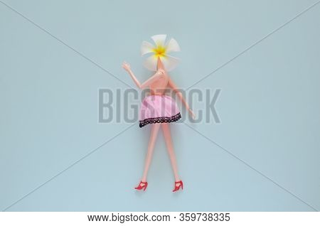 Female Doll Naked On Top Posing With Frangipani Flower. Minimal Beauty And Fashion Concept.