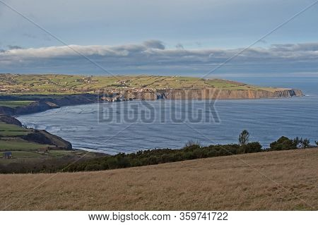 Landscape View Of Coastal Headland Cliffs With Small Seaside Town In Bay