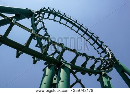 Curved Rollercoaster At A Theme Or Amusement Park Empty Green Metal Tracks And On Blue Sky Backgroun