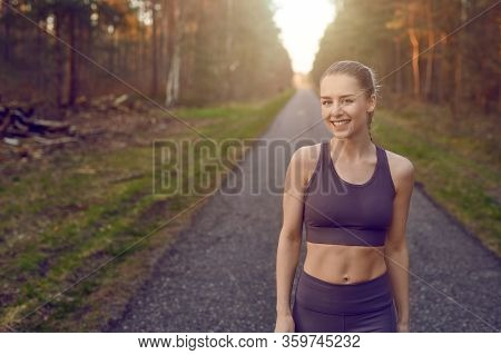 Smiling Athletic Fit Young Woman Working Out On A Tarred Lane Through Forests Backlit By The Warm Gl