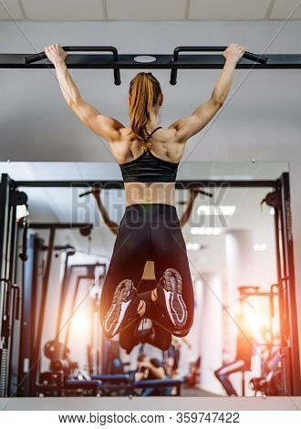 The Sport Girl Pulls Up On The Horizontal Bar In The Gym. Back Photo