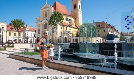Gyor Hungary 06 30 2019: Dad Holds His Little Daughters Hand While Playing With Water At The Vienna