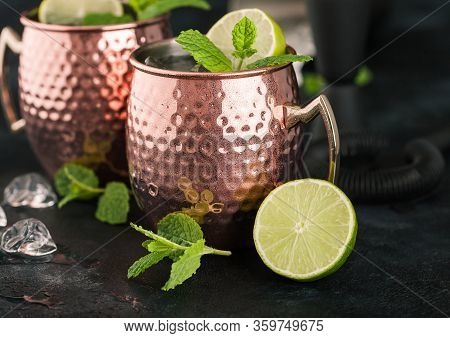 Moscow Mule Cocktail In A Copper Mug With Lime And Mint And Wooden Squeezer On Dark Kitchen Backgrou