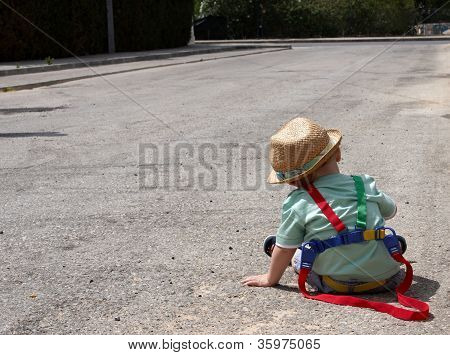 A Toddler Sitting On The Road