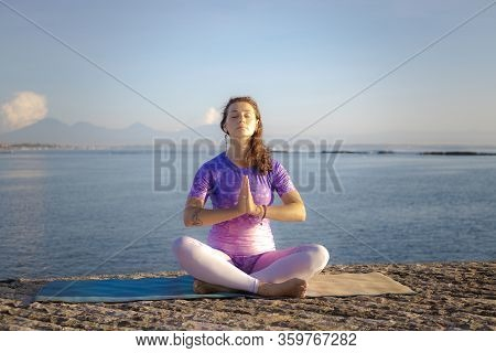 Sunrise Yoga And Pranayama Practice. Young Caucasian Woman Sitting In Lotus Pose. Hands In Namaste M