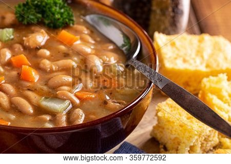 Closeup Of A Bowl Of Tasty Bean Soup With Cornbread On A Wooden Table
