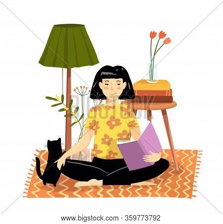 Young Girl Or Woman Sitting On The Floor Rug At Home Reading A Book In Comfortable Cozy Apartment Wi