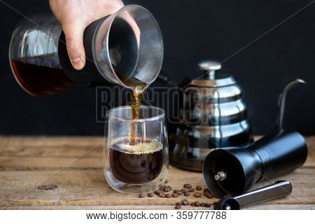 Hot Coffee Is Pouring Into A Glass. Brewing Coffee Through A Funnel. A Cup Of Fresh Hot Filter. A Gr