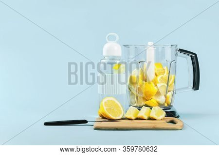 Lemon Water Glass Bottle And A Blender Full Of Bright Yellow Pieces Of Cut Lemons. Front View Copy S