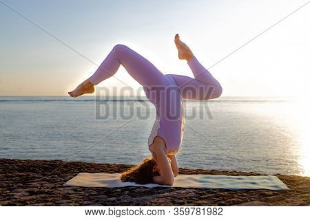 Sunrise Yoga Practice Near The Ocean. Young Woman Practicing Salamba Shirshasana, Yoga Headstand Is
