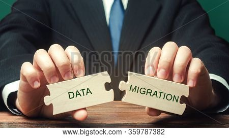 Businessman Collects Wooden Puzzles With The Words Data Migration. Process Of Preparing, Selecting,