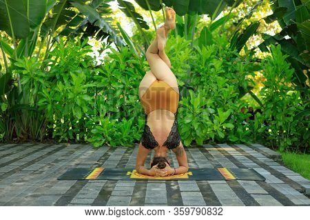 Caucasian Woman Practicing Salamba Sirsasana Pada Garudasana, Headstand Pose Eagle Legs. Outdoor Yog