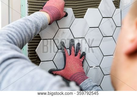 Tiling - Man Laying Marble Texture Hexagon Tiles On The Wall