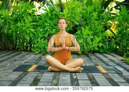 Attractive Caucasian Woman Sitting On Yoga Mat, Meditating, Practicing Yoga And Pranayama. Lotus Pos
