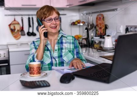 A 65-year-old Woman Works At Home Online By Laptop With Smiling, Talks Via Phone Because Of The Coro