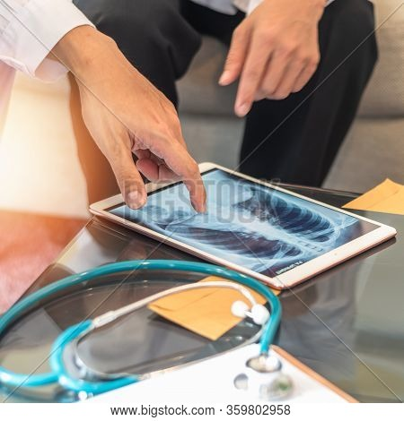 Covid-19 And Doctor Teamwork Diagnosing Lung Infection Disease On X-ray In Digital Tablet With Er Su