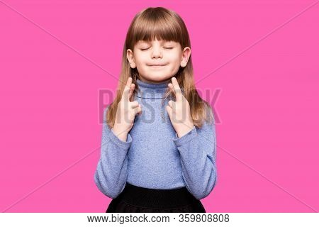Funny Little Girl Crossing Fingers, Hoping Her Wish Come True, Isolated On Pink. Portrait Of Small G
