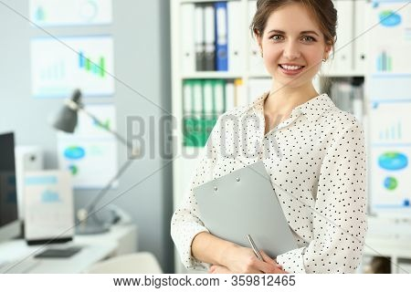 Beautiful Smiling Woman Standing In Office Holding Document Clipped To Pad Looking In Camera Headsho