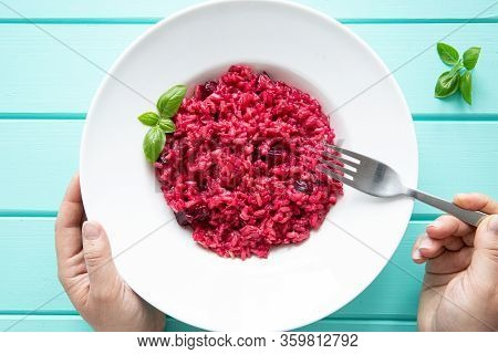 Tasty Italian Risotto With Beetroot On Turquoise Wooden Table, Female Hands Holds Fork, Top View. Ve