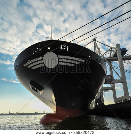 Bow Of Large Ship In Port At Sunset. Under A Light Load She Is Sitting High In The Water Showing The