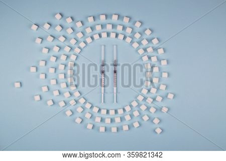 Circle Of Refined Sugar And Insulin Syringes On Blue Background. Type 2 Diabetes. Dose Of Insulin In
