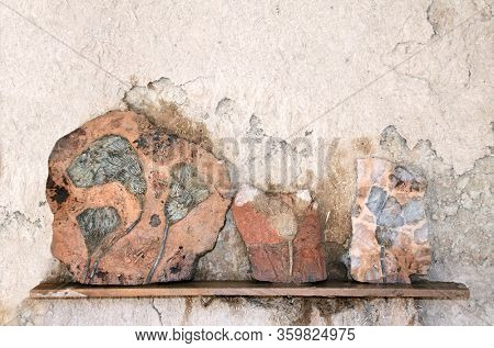 Petrified fossil crinoids (sea lilies, featherstars) in stone on a shelf on an adobe wall
