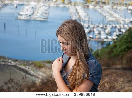 Teen Girl Upset Distraught Emotion Portrait.  She Has Light Brown Long Hair Outdoors With A Marina I