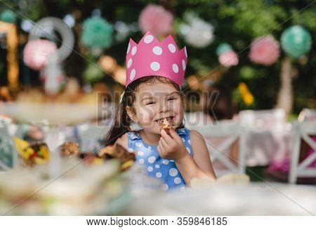 Cheeky Small Girl Outdoors In Garden In Summer, Eating Snacks.