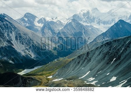 Footpath Through Hills To Beautiful Mountain Valley With Lake. Huge Glacier Mountains Under Gray Clo