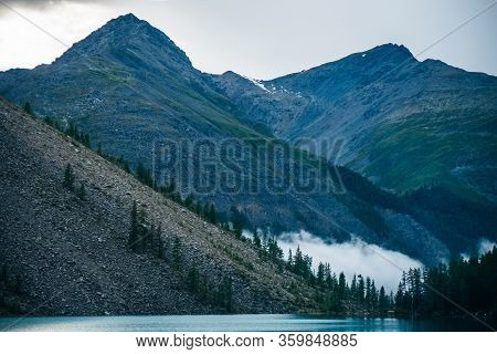 Beautiful Alpine Landscape With Mountain Lake Near Forest On Background Of Huge Mountains In Cloudy