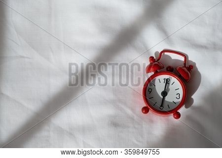 Red Analog Clock On White Rumpled Sheets. Top View, Flat Lay, Copy Spase. Horizontal. Concept Of Awa