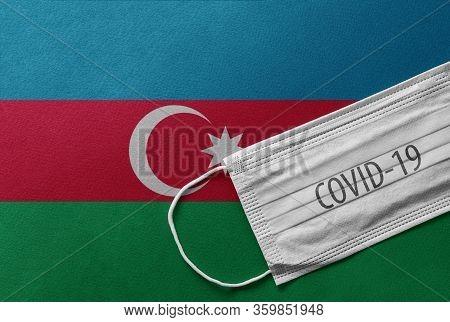 Face Medical Surgical White Mask With Covid-19 Inscription Lying On Azerbaijan National Flag. Corona
