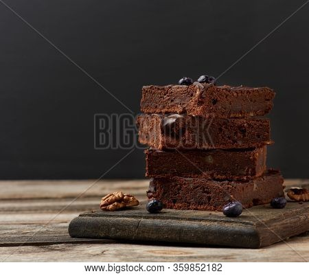 Stack Of Square Baked Slices Of Brownie Chocolate Cake With Walnuts On A Wooden Surface. Cooked Home