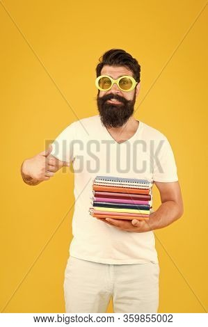 New Releases. Happy Student Pointing Finger At Books Pile. Bearded Man Pointing Index Finger Yellow