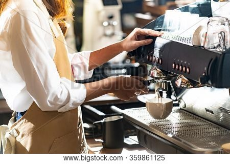 close-up shot of a barista brewing coffee by modern coffeemaker machine to making a cup of coffee with other barista working in background. Using for small business entrepreneur owner concept.