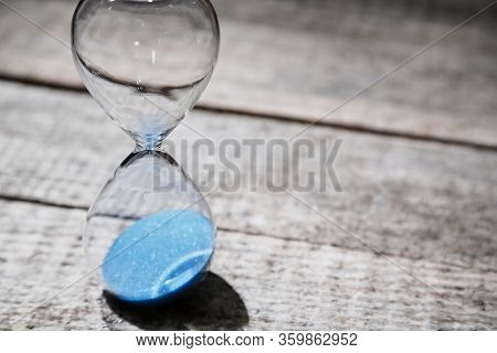 Business Deadline. Time Passing. Time-limit. Urgency And Running Out Of Time. Hourglass On Wooden Su