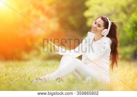 Happy woman with headphones relaxing in the spring park. Beauty nature scene with colorful background. Fashion woman enjoying the music from her mobile phone in summer season. Outdoor lifestyle