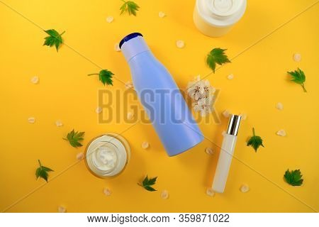 Bottles And Jars Of Moisturizing, Nourishing Face And Body Creams With Fresh Green Leaves On A Yello