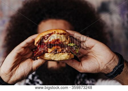 Curly hipster holding  craft mouth-watering bacon and angus beef burger flavored with crunchy fried