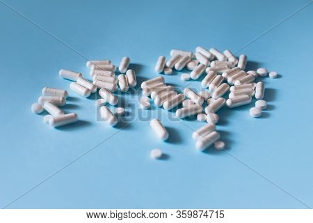 White Medical Pills And Capsules Or Vitamines On Blue Background. Place For Text.
