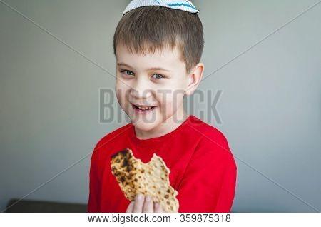 Cute Caucasian Child In A White Kippah Cap Eating Shmura Matzo, A Piece Of Traditional Jewish Unleav