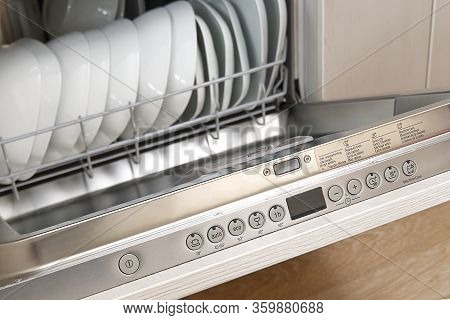 Full Loaded Dishwasher Machine. Integrated Dishwasher With White Plates Front Vew.