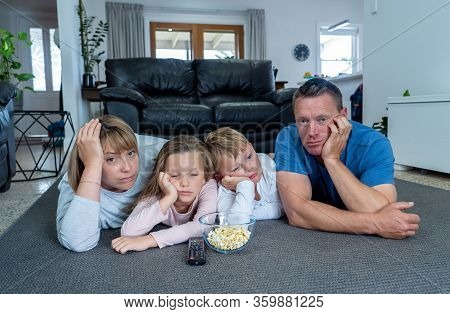 Covid-19 Outbrek. Bored Family Confined To Their Home Watching Tv During Coronavirus Lockdown