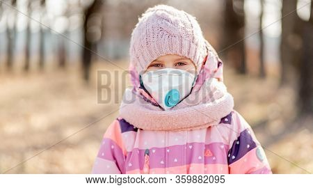 Prety little girl in medical mask on nature background